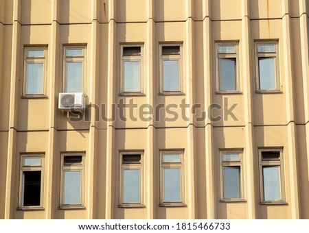 Photo of  Panoramic view of a modern design business center building with laconic decorative details in warm yellow