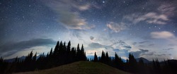 Panoramic view of a mountain hill facing spruce forest and a mountain ridge, magical starry night sky with purple clouds above beautiful horizon, copy space. Concept of travelling, galaxy and nature.