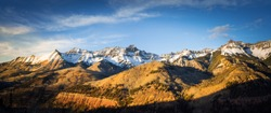 Panoramic view of a mountainside lit by a setting sun in the rocky mountains.  The glow of the sun illuminates the fall colors, along with the first snow found high up in the mountain peaks.