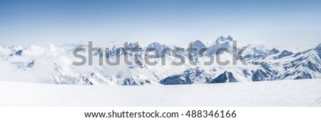 Panoramic view of a Mt. Elbrus ski slope and snowy Greater Caucasus mountains on the horizon at winter cold sunny day. #488346166