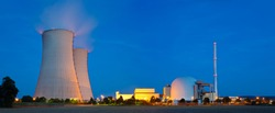 Panoramic view of a nuclear power plant with night blue sky.