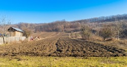 panoramic view of a plowed field, a forest on the horizon and the blue sky. Agricultural land plowed. Beautiful landscape in the countryside