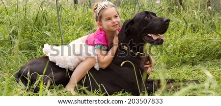 Panoramic view of a pretty young girl wearing a pink fancy dress, sitting on her dogs back enjoying a sunny holiday in a green park field, hugging him outdoors. Active family with pets, lifestyle.