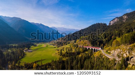 Panoramic View of a red train crossing the Landwasser Viaduct in the Swiss Alps