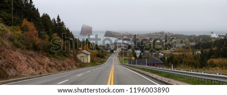 Panoramic view of a road leading to a beautiful modern town on the Atlantic Ocean Coast during a hazy day. Taken in Percé, Quebec, Canada.