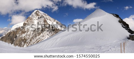 Panoramic view of a snow covered mountain peak, with a further peak in the background and blue sky with fluffy clouds,