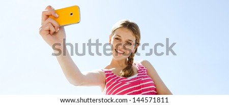 Panoramic view of a teenager girl using her smartphone to take photographs while standing against an intense blue sky background, smiling and having fun.