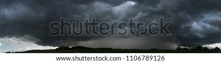 panoramic view of a terrifying dark thunderstorm approaching