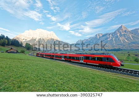 Panoramic view of a train traveling on green fields with Mountain Zugspitze in background on a beautiful sunny day in Lermoos, Tirol Austria ~ Beautiful autumn scenery of idyllic Tyrolean countryside