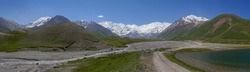 Panoramic view of Achik Tash basecamp of Lenin Peak nowadays Ibn Sina peak in the snow-capped Trans-Alai mountain range in southern Kyrgyzstan with river and lake in the foreground