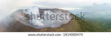 Panoramic view of active Nyiragongo volcano with lava lake emitting smoke with more volcanoes in background