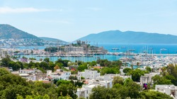 Panoramic View of Aegean sea, traditional white houses marina and Bodrum Castle in Bodrum city of Turkey. Aegean style colorful street, wall, house and flowers in Bodrum town Turkey.