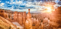 Panoramic view of amazing hoodoos sandstone formations in scenic Bryce Canyon National Park in beautiful golden morning light at sunrise with dramatic sky and blue sky, Utah, USA