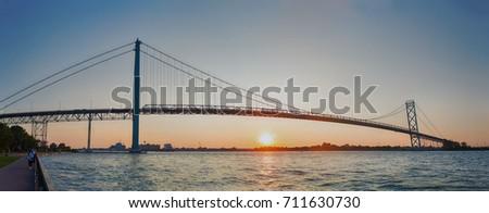 Panoramic view of Ambassador Bridge connecting Windsor, Ontario to Detroit Michigan at sunset