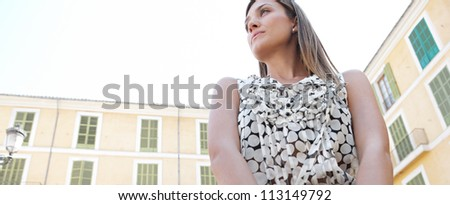 Panoramic view of an attractive businesswoman against classic buildings.