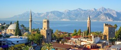 Panoramic view of Antalya Kaleici Old Town with the Clock Tower, Yivli Minaret, Tekeli Mehmet Pasa mosque, Mediterranean Sea and the Taurus Mountains in background, Turkey