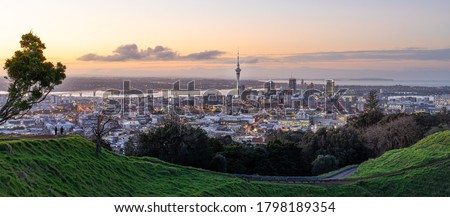 Panoramic view of Auckland city skyline with Auckland Sky Tower from Mt. Eden at sunset New Zealand