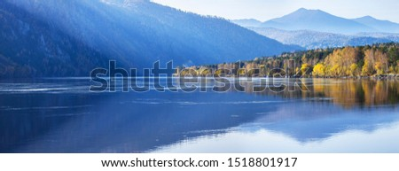 Photo of  Panoramic view of autumn nature. The wide Yenisei River in Siberia. Blue sky, forested slopes and beautiful reflection.