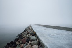 Panoramic view of Baltic sea from sandy shore. Promenade to the lighthouse, breakwaters. Thick white fog, mist. Waves, water splashes, long exposure. Seascape. Picturesque monochrome scenery