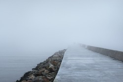 Panoramic view of Baltic sea from sandy shore. Promenade to the lighthouse, breakwaters. Walking people. Thick white fog, mist. Waves, water splashes, long exposure. Seascape. Monochrome scenery