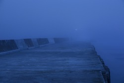 Panoramic view of Baltic sea. Port entrance, lighthouse, breakwaters. Thick fog, mist, blue light. Waves, water splashes, long exposure. Seascape. Monochrome scenery. Danger, safety concepts