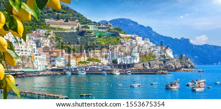 Photo of  Panoramic view of beautiful Amalfi on hills leading down to coast, Campania, Italy. Amalfi coast is most popular travel and holiday destination in Europe. Ripe yellow lemons in foreground.