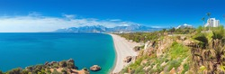 Panoramic view of beautiful blue lagoon and Konyaalti beach in popular resort city Antalya, Turkey. Sunny day, high mountains on horizon.