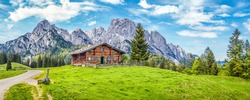 Panoramic view of beautiful mountain scenery in the Alps with traditional rural mountain chalet and fresh green meadows on a sunny day with blue sky and clouds in spring