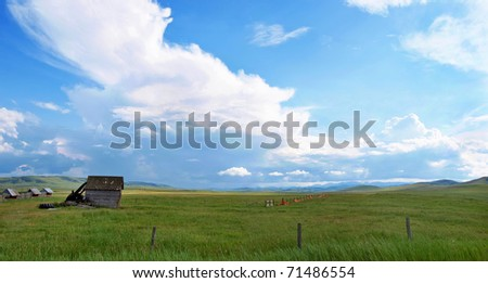 Panoramic view of beautiful prairie landscape with old barn and blue sky and clouds in Alberta, Canada