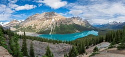 Panoramic view of beautiful turquoise waters of the Peyto Lake with snow-covered peaks above it in Rocky Mountains, Banff National Park, Canada.