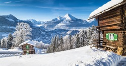Panoramic view of beautiful white winter wonderland mountain scenery in the Alps with traditional mountain chalets on a cold sunny day with blue sky and clouds