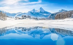 Panoramic view of beautiful white winter wonderland scenery in the Alps with snowy mountain summits reflecting in crystal clear mountain lake on a cold sunny day with blue sky and clouds
