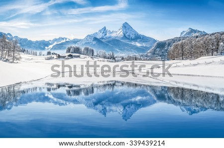 Panoramic view of beautiful white winter wonderland scenery in the Alps with snowy mountain summits reflecting in crystal clear mountain lake on a cold sunny day with blue sky and clouds #339439214