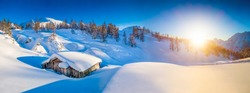 Panoramic view of beautiful winter mountain landscape with traditional mountain cabin in the Alps in golden evening light at sunset