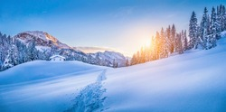 Panoramic view of beautiful winter wonderland mountain scenery with traditional mountain cabin the background in the Alps in golden evening light at sunset