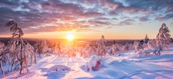 Panoramic view of beautiful winter wonderland scenery in scenic golden evening light at sunset with clouds in Scandinavia, northern Europe