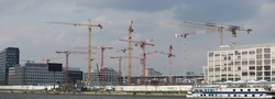 panoramic view of Berlin; modern buildings and cranes near Spree river