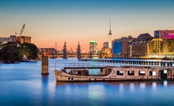 Panoramic view of Berlin skyline with famous TV tower and Oberbaum Bridge with old ship wreck lying in river Spree in twilight during blue hour at dusk, Berlin Friedrichshain-Kreuzberg, Germany