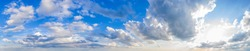 Panoramic view of blue sky with clouds and sun.