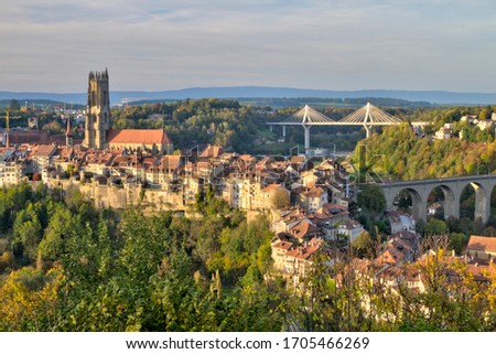 Panoramic view of cathedral of St. Nicholas, new Poya and old Zaehringen bridge by night, Fribourg, Switzerland, HDR