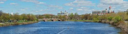 Panoramic view of Charles River and Harvard University campus in early spring. Cambridge, Massachusetts, USA. Weeks Bridge, colorful domes of student residences, people rowing in the Charles.