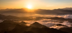 Panoramic view of china mountains - Sunrise, the sea of clouds, mountains and valleys. Warm orange sunrise and rays of sunshine, National forest scenic area in Hunan Province China. Morning fog