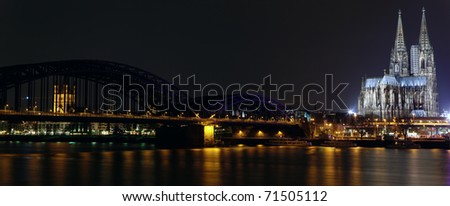Panoramic view of Cologne Gothic Cathedral and railway bridge at night as seen from the Rehin