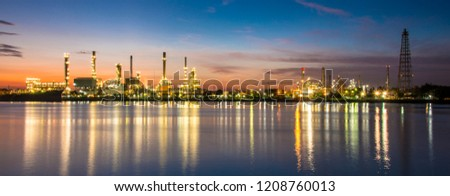 Panoramic view of colorful picture of oil refinery plant/petrochemistry industry in twilight time with river in slow shutter speed foreground.