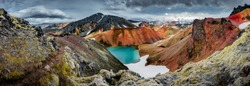 Panoramic view of colorful rhyolite volcanic mountains Landmannalaugar as pure wilderness in Iceland and a hidden highland lake, Iceland, summer time