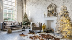 Panoramic view of cozy living room with loft interior, comfort sofa, armchair near decorative fireplace and decorated new year tree in modern apartment. Lovely house with bright lounge room