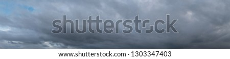 Panoramic View of Dark Storm Clouds During a Winder Day #1303347403