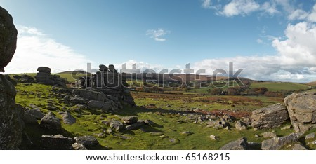 Panoramic view of Dartmoor in Devon with granite rocks in foreground - stock photo
