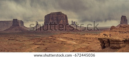 Panoramic view of desert landscape with horse in Monument Valley, Monument Valley Navajo Tribal Park. USA