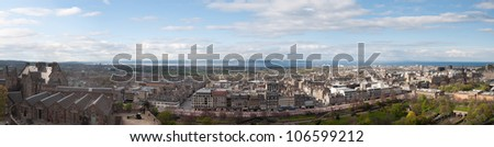 Panoramic view of Edinburgh on a sunny day from the castle hill, with the castle flanks on the left